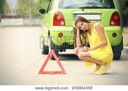 Upset young woman sitting near red emergency stop sign and broken car on background