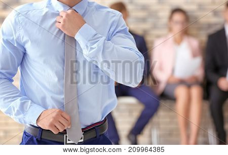 Young man and blurred people on background