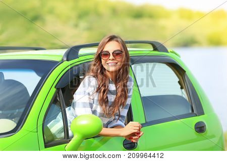 Beautiful young woman in car on river shore