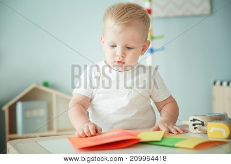Cute boy with handmade greeting card at home
