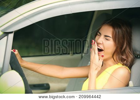 Tired young woman in car