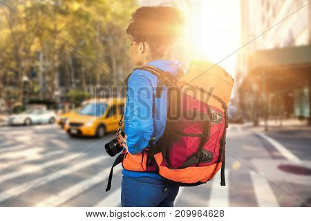 Young woman with backpack holding camera against new york street