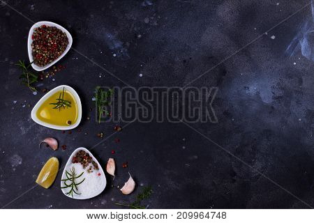 Food background - spices and salt with olive oil on black background