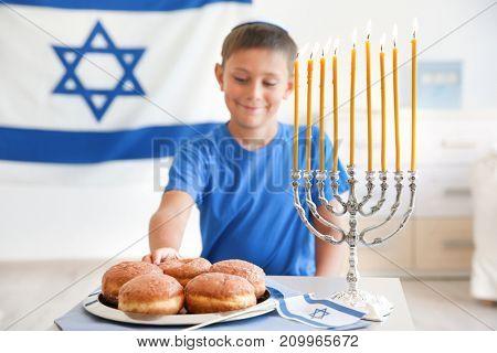 Jewish boy with traditional sufganiyah at home
