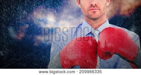Businessman with boxing gloves against low angle view of snow covered mountain