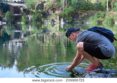 Young man near lake in forest