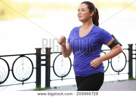 Overweight young woman jogging near river. Weight loss concept