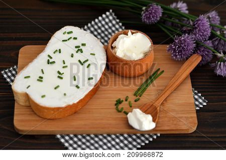 Cream cheese and chives on wooden board