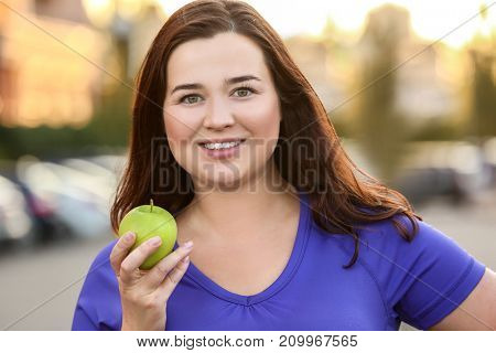 Overweight young woman with green apple outdoors. Weight loss concept