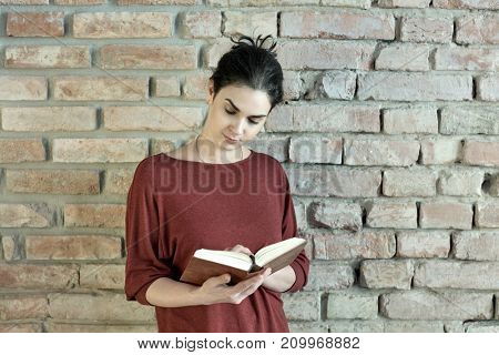 Casual young adult woman standing at wall holding and reading book. Lifestyle portrait photo with copyspace.