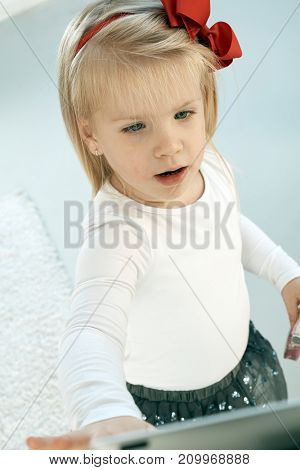 Closeup photo of adorable little blonde girl in pretty clothes.