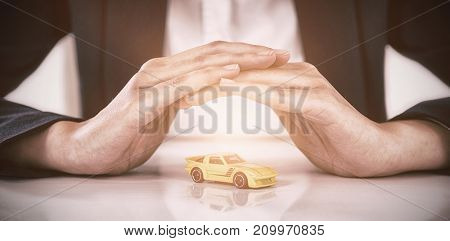Mid section of businesswoman protecting toy car with hands