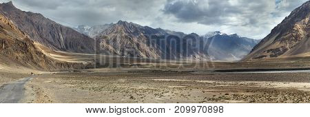 Panorama photo high mountains valley: wide brown hills canyon under gray evening sky with clouds fog lies on the slopes Tibet.