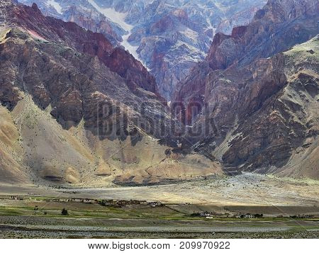 The village in the mountain valley: a huge colored wall of the gorge red burgundy and yellow rocks at the foot of a small village among green fields summer in the Himalayas.