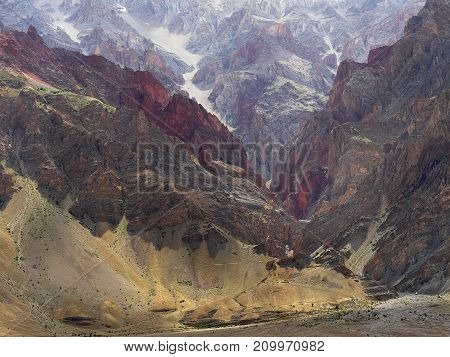 Magnificent huge color mountain wall: claret red and yellow rocks alternate with each other Zanskar Tibet Himalayas.