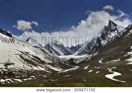 Glacial valley in the high mountains of the Himalayas: the slopes of the peaks are covered with snow the glacier drains into the green valley white clouds lie on the peaks of the peaks.