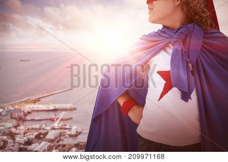 Boy wearing superhero costume  against view of city and harbor
