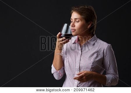 Beautiful girl with a glass of red wine on a black background. A girl with a short hair smells the aroma of wine. Brunette. Close-up.