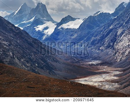 High mountains glacial valley in the Himalayas: a huge peak covered with snow towers over the peaks a river flows along the bottom of the valley the slopes are overgrown with yellow vegetation.