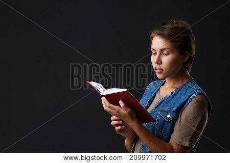 Attractive girl with short hair is reading a red book on a black background. Close-up