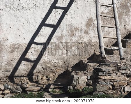 Old wooden staircase is leaning against a white wall a shadow from the stairs falls on the wall stones in the basement a modern interior design photo.