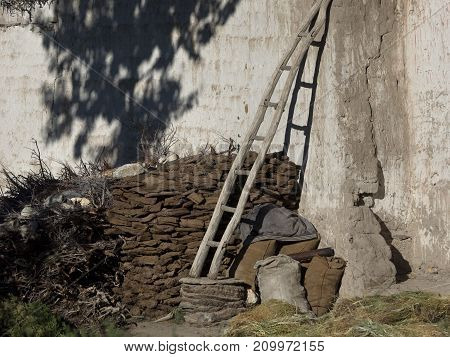 Wooden staircase leaning against a white clay wall the back of the wall is firewood on the wall there is a shadow from a tree summer in the Himalayas.
