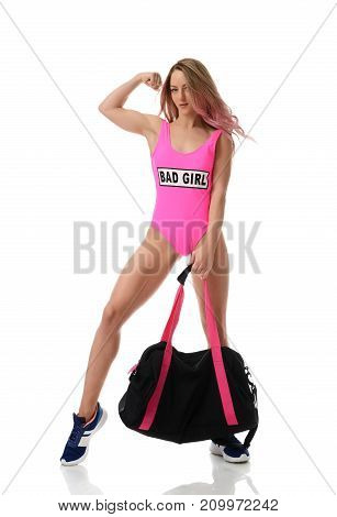 Beautiful caucasian female athlete with gym bag in pink body. Young woman in sportswear carrying gym bag looking at camera