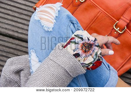 Young hipster woman is sitting on a wooden surface with a trendy colorful bag. Top view shot, body parts. Fashion happy life autumn concept.