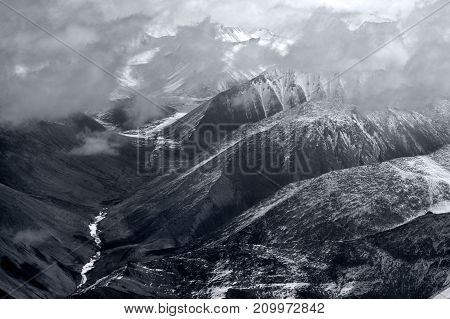 High mountains of the valley of the Western Himalayas: waves of mountain ridges are dissected by a deep gorge at the bottom is a river shining Northern India a black and white photograph.