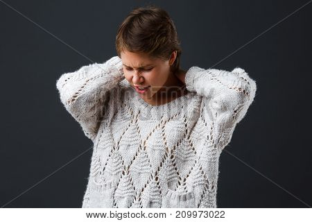 Dark-haired beautiful girl with short hair on a black background holds her hands behind her neck. Pain. Pain in the neck. Close-up.