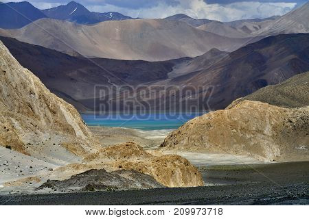 Lake Pangong: among the mountain ranges are light brown and dark in color like a precious stone in the frame you can see the aquamarine water pond the Himalayas Northern India.