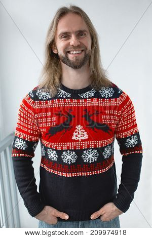 A man in a New Year's sweater with a deer ornament.