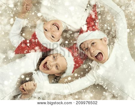 happy child lying together on wooden background, dressed in christmas Santa hat and having fun, winter holiday concept, snow decoration, yellow toned