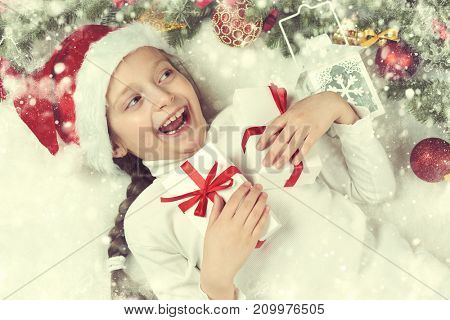 girl child lie in christmas decoration on white fur, yellow toned, face closeup, dressed in santa hat, winter holiday concept, xmas tree
