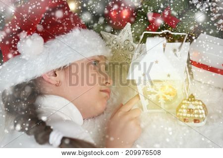 child girl lie with candle lantern and dream, christmas decoration, face closeup, dressed in santa hat, winter holiday concept