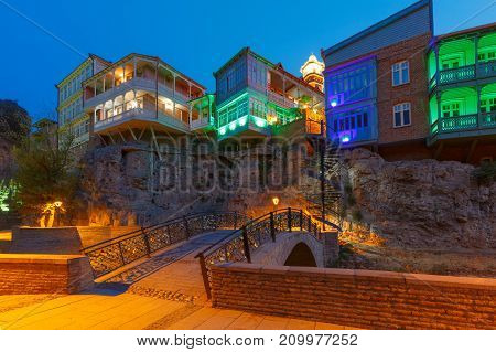 Amazing View of Jumah Mosque, Sulphur Baths, bridge and famous colorful balconies in old historic district Abanotubani in night Illumination during morning blue hour, Tbilisi, Georgia.