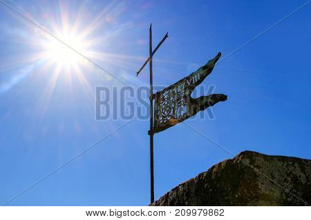 Metal Flag On The Top Of Montalcino Fortress Tower Against Blue Sky With Sunburst, Val D'orcia, Tusc
