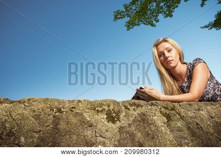 Technology outdoor relaxation concept. Woman sitting in park relaxing and using mobile phone spending her leisure time outside