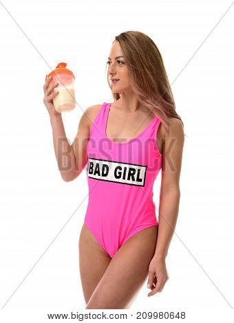 Beautiful caucasian female athlete with gym bag in pink body. Young woman in sportswear carrying gym bag looking at cocktail