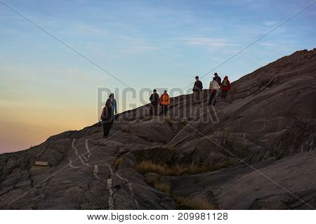 Mount Kinabalu,Ranau,Sabah,Malaysia-March 12,2016:Group of adventure climber moving down from the summit of Mountain Kinabalu during sunrise at the majestic Mountain Kinabalu,Sabah,Malaysia.