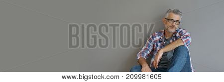 Trendy 40-year-old man sitting on floor, template