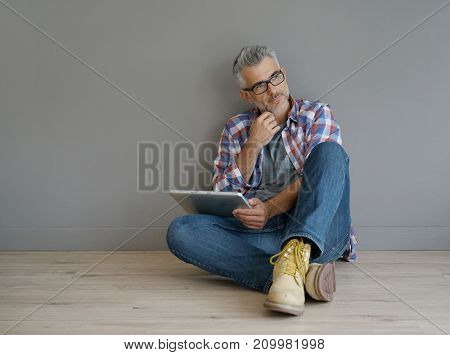 Trendy 40-year-old man sitting on floor with tablet, isolated
