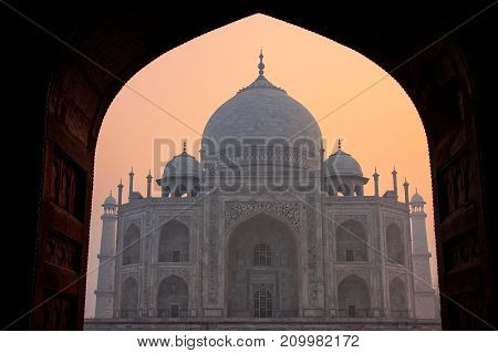 Taj Mahal at sunrise framed with the arch of the mosque Agra Uttar Pradesh India. Taj Mahal was designated as a UNESCO World Heritage Site in 1983.