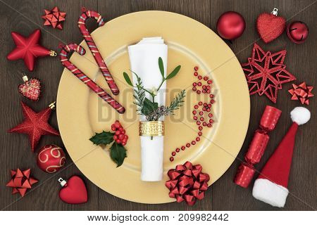 Christmas table place setting with gold dinner plate, napkin, holly, ivy, mistletoe and cedar, candy canes, cracker, santa hat and red decorations on oak wood background.