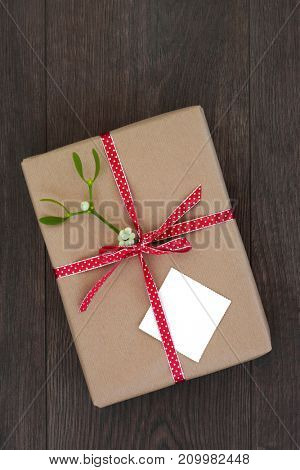 Christmas gift box wrapped in brown paper with red polka dot ribbon with mistletoe on oak background. Top view of holiday giving and love concept.