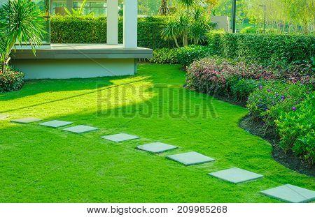 Pathway in garden,green lawns with bricks pathways,garden landscape design poster