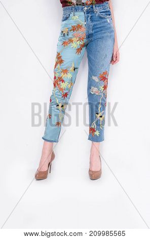 Fashion. Woman legs in embroidered flowers ,bird jeans and high heels shoes posing in studio