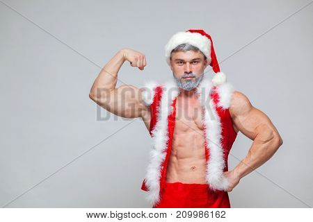 Christmas. Sexy Santa Claus . Young muscular man wearing Santa Claus hat demonstrate his muscles