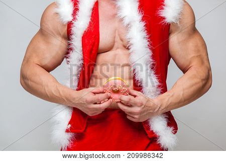 Holidays and celebrations, New year, Christmas, sports, bodybuilding, healthy lifestyle - Muscular handsome sexy Santa Claus enjoys fresh baked piping hot donuts left for him as a thank you gift for all the nice presents he brings to good little boys and