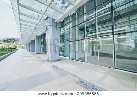 Modern empty office buildings with glass wall and empty pavement .
